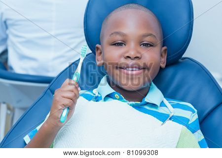 Portrait of young boy holding toothbrush in the dentists chair