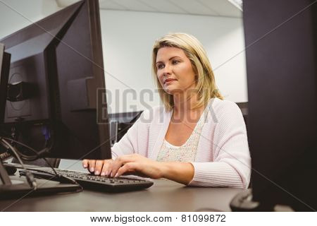 Cheerful mature student using laptop in the office