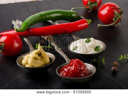Mustard, Ketchup And Mayonnaise On A  Black Table.