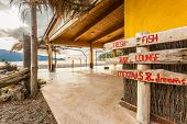 pic of wooden shack  - Wooden sign at beach bar on Bussaglia beach near Porto on west coast of Corsica - JPG