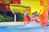 stock photo of chute  - children sliding down a water slide in summer time - JPG