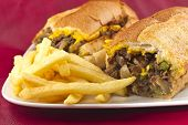 stock photo of cheesesteak  - A messy Philly Cheesesteak with onions peppers and mushrooms fries on the side  - JPG