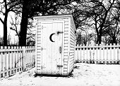 stock photo of outhouses  - Vintage outhouse with picket fence in black and white in the American midwest in Winter - JPG