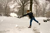 stock photo of snow shovel  - A young woman throwing snow while shoveling - JPG
