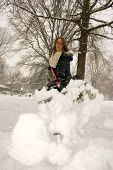 pic of snow shovel  - A young woman throwing snow off the shovel - JPG
