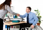 image of workplace accident  - man in wheelchair is greeting a woman in the office - JPG