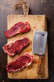 image of ribeye steak  - Raw fresh meat Ribeye steak entrecote and meat cleaver on cutting board on wooden background - JPG