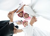 foto of arabic  - Happy group of Arabic people with heads together in circle over sky background - JPG