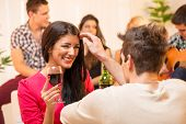 stock photo of caress  - The young man at the house party is courting the pretty brunette caressing her hair and in the background you can see a small group of young people having fun at a party.
