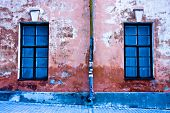 stock photo of downspouts  - Cracked red wall with two windows and downspout - JPG