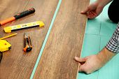 image of laminate  - Carpenter worker installing laminate flooring in the room - JPG