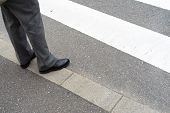 stock photo of slag  - Man legs in slag pants with shoes waiting to cross the street at a crosswalk - JPG