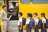 stock photo of bus driver  - Cute schoolchildren waiting to get on school bus outside the elementary school - JPG