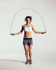 stock photo of jumping  - Fit young woman skipping rope. Portrait of muscular young woman exercising with jumping rope on grey white background. ** Note: Soft Focus at 100%, best at smaller sizes - JPG