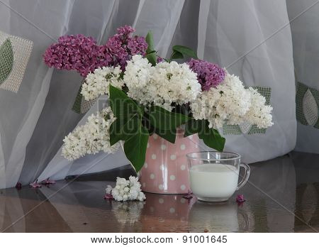 Lilac Bouquet In A Transparent Jug And A Cup With Milk