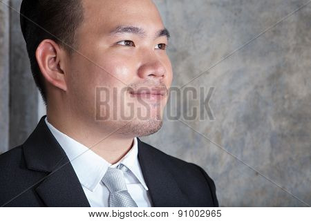 Close Up Skin On Face Of Young Asian Business Man Looking To Forward Against Cement Wall Copy Space