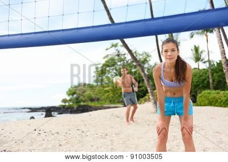Beach volleyball serve - man serving in beach volley ball game on beautiful summer day. Young people having fun in the sun living healthy active sports lifestyle outdoors. Woman and man.