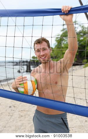Beach volleyball man in sporty active lifestyle portrait holding volley ball after game on summer beach. Handsome topless shirtless male fitness model living healthy lifestyle doing sport on beach.