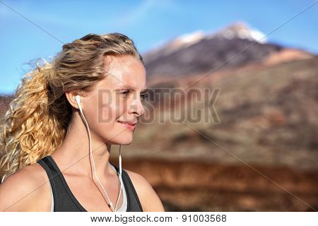 Running girl with earphones - woman runner listening to music in earbuds. Female athlete portrait after running in beautiful nature. Healthy lifestyle concept with beautiful young blonde fitness model