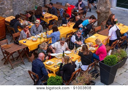 CORNIGLIA, ITALY - APRIL 12, 2015: Unidentified people eating traditional italian food in outdoor restaurant of Corniglia, Italy. Corniglia is one of five famous coastline villages in the Cinque Terre