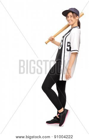 Full length profile shot of a young woman in a baseball jersey, holding a baseball bat and leaning against a wall isolated on white background