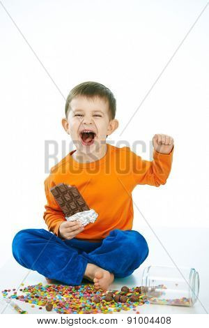 Naughty little kid eating chocolate sitting cross-legged on floor, sweets spilt. Laughing, hand in hair, isolated on white.