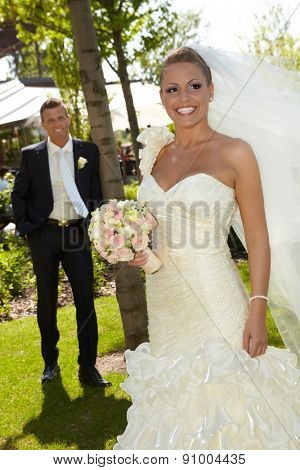 Beautiful woman in wedding gown smiling happy on wedding-day, wearing long veil, groom at background.