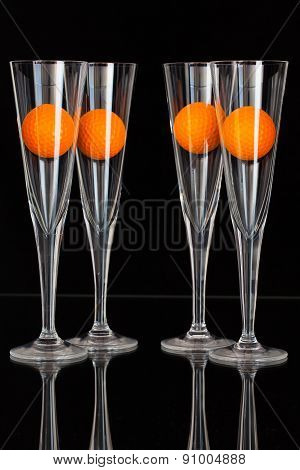 Four Glasses Of Champagne With Orange Golf Balls