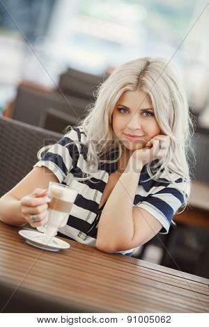 Pretty young woman sitting in a cafe with a cup of coffee latte