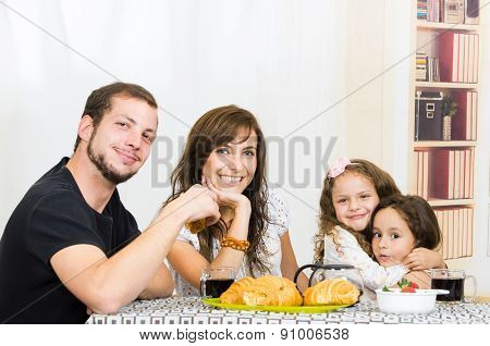 Beautiful young happy family eating meal