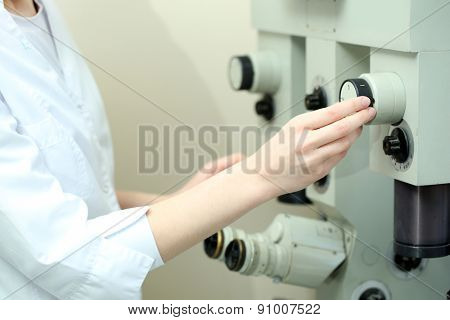 Female scientist looking through a microscope in laboratory