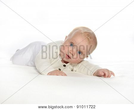 baby girl child lying down on white blanket fashion portrait face studio shot isolated on white caucasian