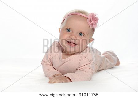 Caucasian baby girl lying down on white blanket smiling  portrait isolated on white