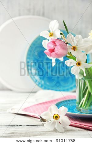 Spring bouquet in glass mug on color wooden background