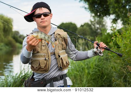 Fisherman caught a perch and holds it in his hands.