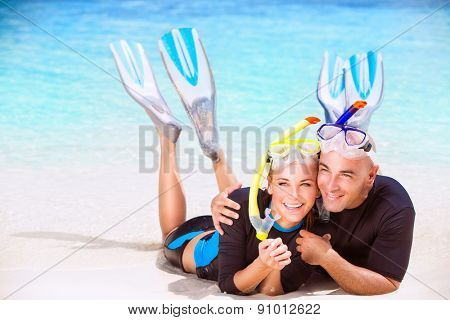 Happy couple enjoys beach activities, tourists lying down on sandy coast and hugging each other, wearing snorkeling gear, water sport, spending honeymoon vacation on beach resort