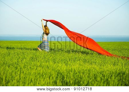 Young happy woman in wheat field with fabric. Summer lifestyle