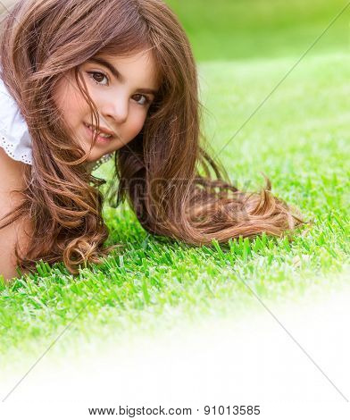 Closeup portrait of cute little girl lying down fresh green grass field, having fun outdoor on backyard, happy childhood concept, white copy space