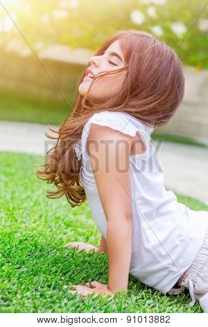 Little baby girl meditating outdoors, relaxation and zen balance, stretching and doing yoga exercises for kids on fresh green grass field, healthy lifestyle and wellness