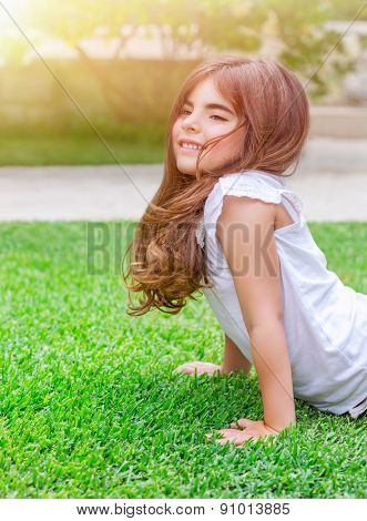 Cute little girl with pleasure doing push-ups outdoors, exercising on fresh green spring field in sunny day, health lifestyle, active childhood concept
