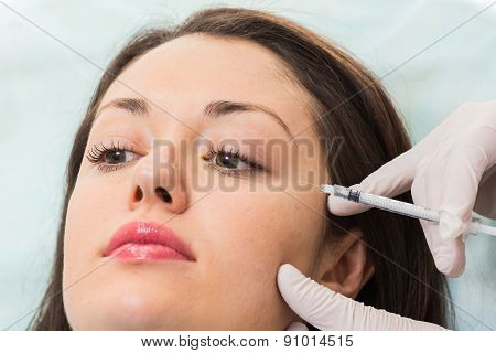 Beautician makes injection into the patient's face in spa salon