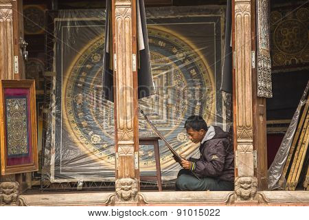 BHAKTAPUR, NEPAL - CIRCA DEC, 2013: Unidentified Nepalese man working in the his painting workshop. More 100 cultural groups have created an image Bhaktapur as Capital of Nepal Arts.