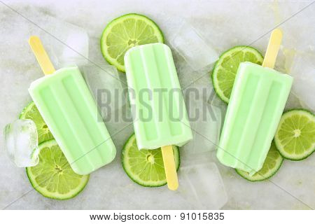 Lime yogurt popsicles with fresh lime slices on white marble