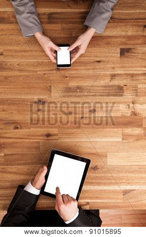 Man and woman working on smart phone and tablet. Shot from above view