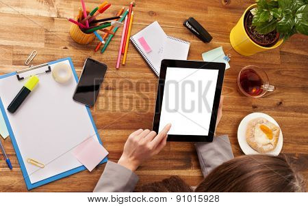 Young woman working with tablet placed on wooden desk with blank screen for text. Shot from aerial view