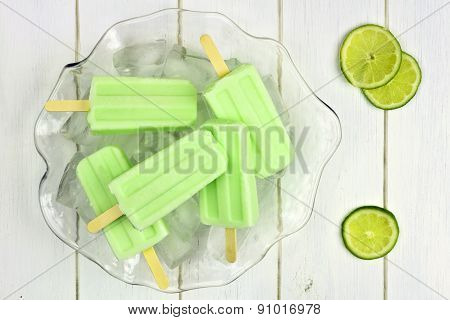 Lime yogurt popsicles in a bowl against white wood