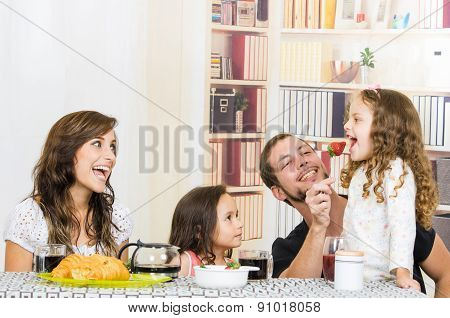 Cute family with two girls eating breakfast