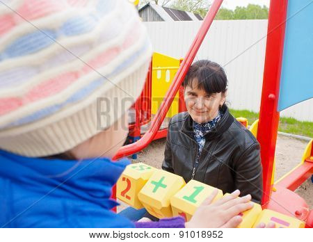 Mother Watching Her Daughter, Counting On The Dice On The Playground