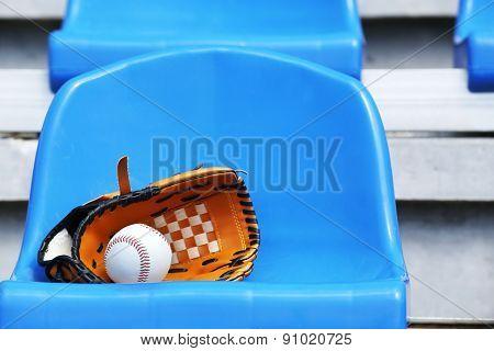 Baseball ball and glove on stadium seat