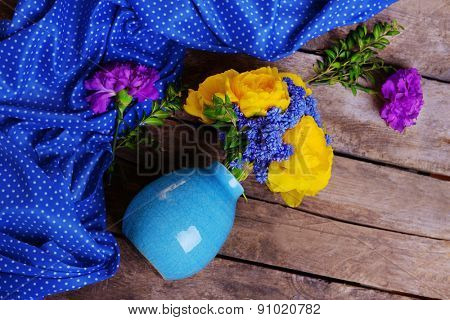 Beautiful flowers in vase on wooden background top view